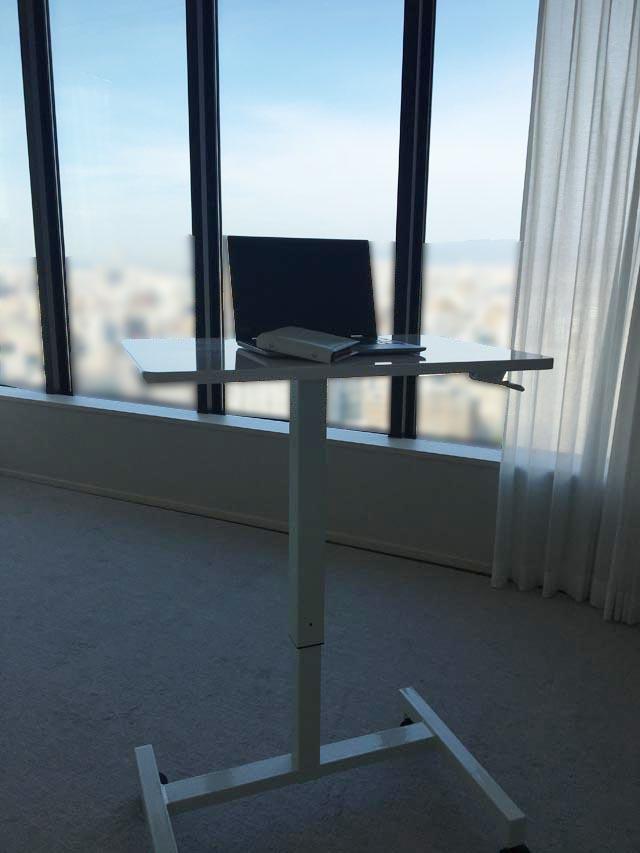 外の景色を見ながら昇降式スタンディングデスクでパソコンをしている様子,勉強机,学習机,パソコンデスク,高さ調節ができる机,
