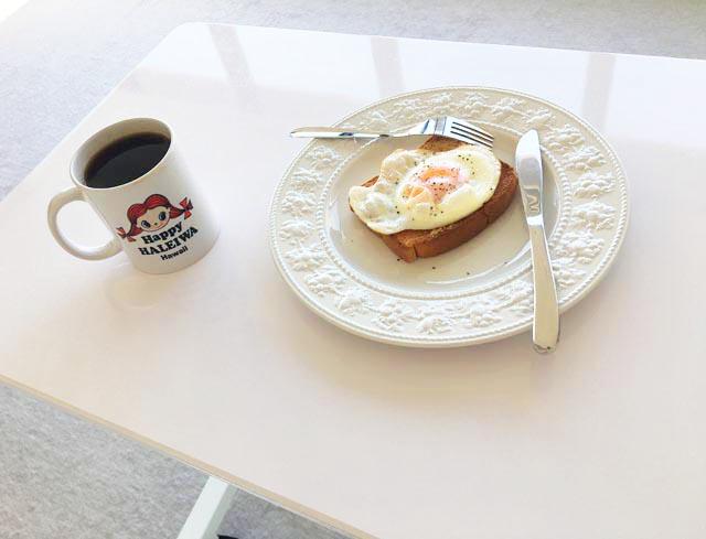 昇降式スタンディングデスの上にパンとコーヒーが置かれている,