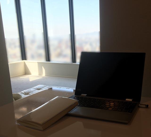 景色を見ながら,スタンディングテーブルでパソコンをしている様子,
