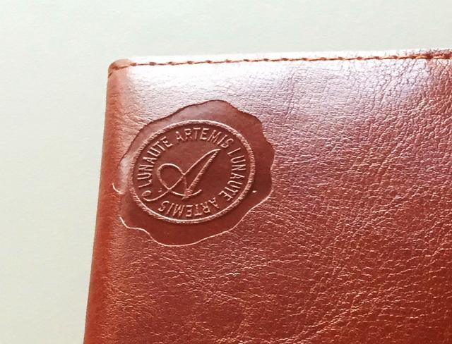 ノートカバー,左上には、スタンプで押されたようなワンポイントがついている,