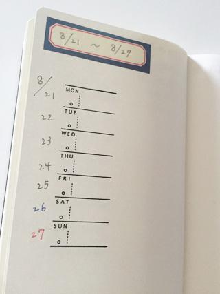 ノートに週間スケジュールのスタンプが押されていて、上部にKITTAのフレーム柄がシールが貼られている